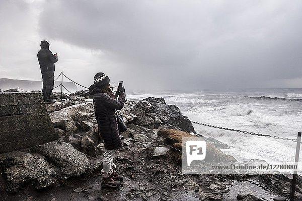 Tourists taking pictures to a rough sea near Kirkjufjara beach (region of Suðurland  Iceland).
