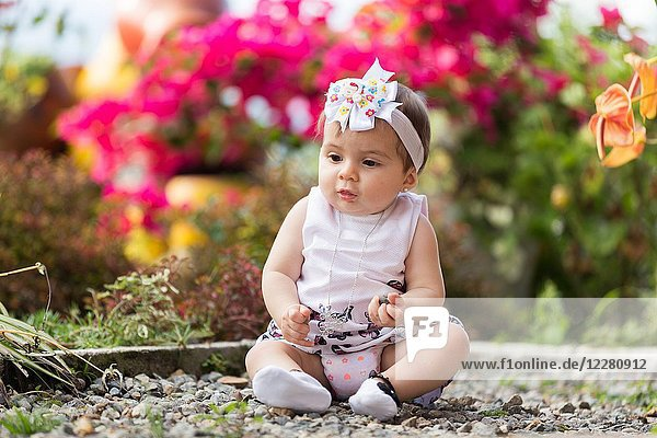 Little girl sitting in the garden playing with rocks.