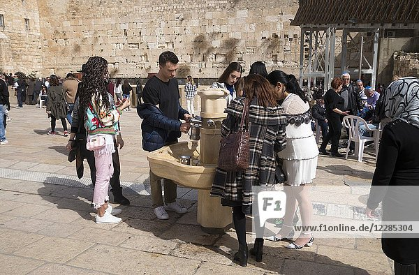 Jewish women washing hands before praying at the Western Wall. The Western Wall  or 'Wailing Wall'  is the most religious site in the world for the Jewish people  located in the Old City of Jerusalem. Western Wall area. Street scene in The Jewish Quarter of Jerusalem's Old City is one of the four quarters of the walled city. The quarter is home to around 2  000 people and covers about 0. 1 square kilometers. It is also the location of many tens of synagogues and yeshivas (places of the study of Jewish texts) and has been almost continually home to Jews since the century 8 BCE.