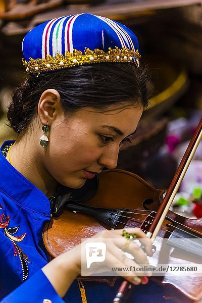 A Uyghur woman playing a violin  International Grand Bazaar  Urumqi  Xinjiang Province  China.