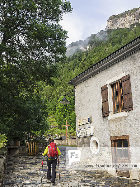 Woman hiker passing by an old building in the village of Gavarnie  France
