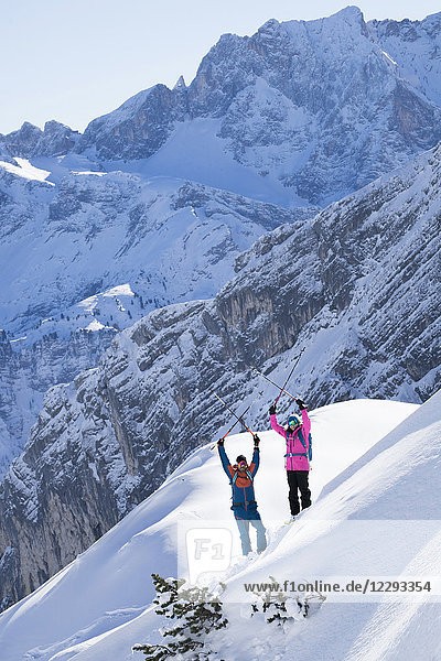 Skiers raising arms with ski poles