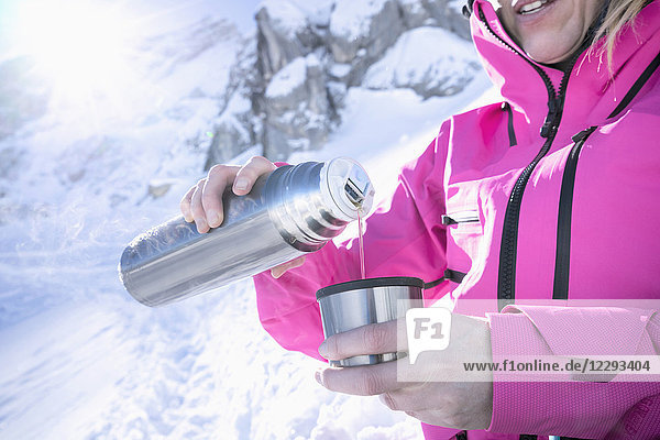 Woman skier pouring hot tea from drinks flask Woman skier pouring hot tea from drinks flask,