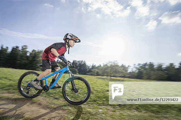 Little boy speeding on mountain bike