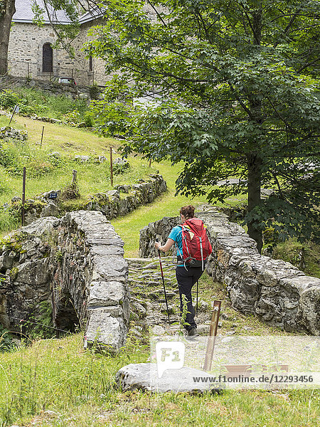 Woman hiking in the High Pyrenees on old bridge in village of Heas  France
