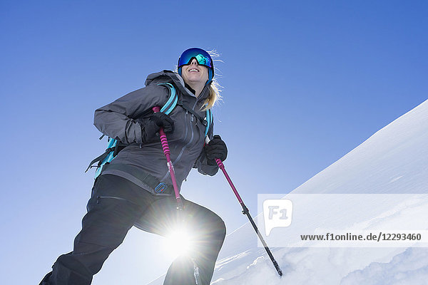 Low angle view of a woman skiing under bright sunlight