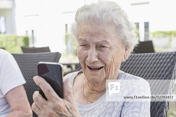 Senior woman smiling and using smart phone