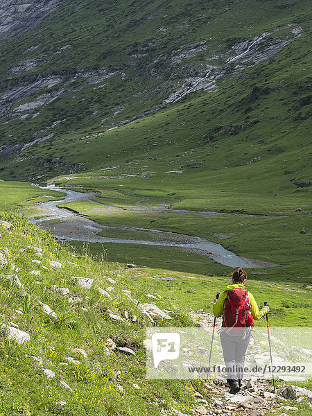 Woman hiking in the High Pyrenees descending from Hourquette d'Alans towards Pont d'Estaube  Gavarnie  France