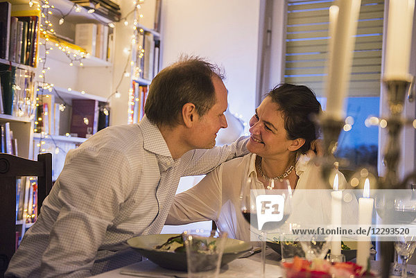 Couple embracing each other at a candlelight dinner