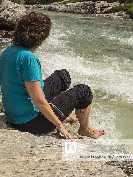 Woman hiker taking rest at riverbank of Gaube d'Estaube  France