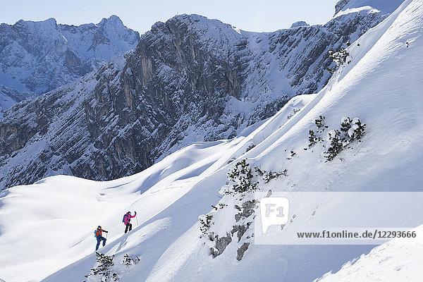 Couple climbing up the ski slope