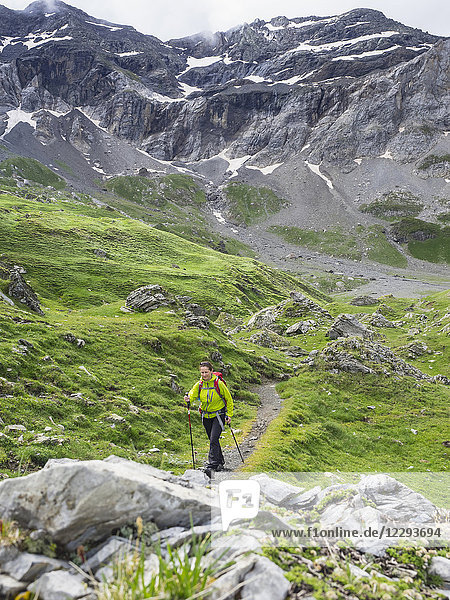 Woman hiking in the High Pyrenees on small path through Cirque de Troumouse  France