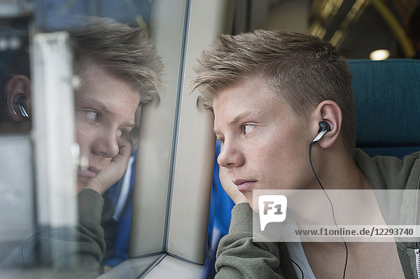 Boy listening music on headphones and looking out of window in train