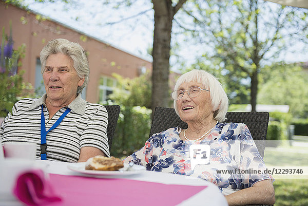 Two senior women sitting outdoors