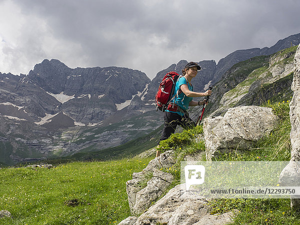 Woman hiking in the High Pyrenees view of cirque d'Estaube in background  Gavarnie  France