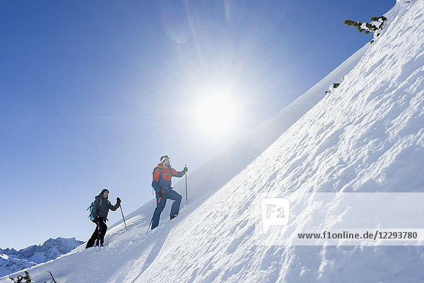 Couple climbing up the ski slope in Upper Bavaria Couple climbing up the ski slope in Upper Bavaria