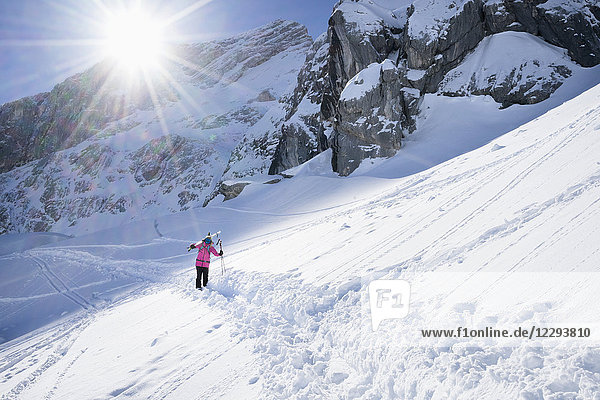 Woman carrying her ski and walking in snow