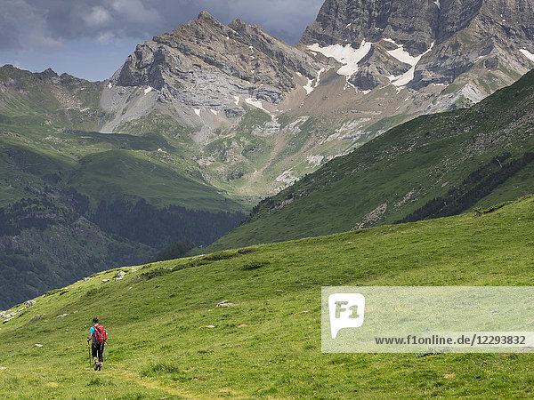 Woman hiking in the High Pyrenees descending Oulettes d'Ossoue towards Gavarnie  France