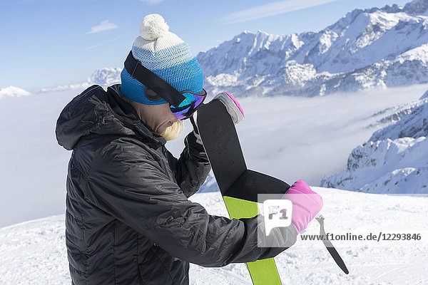 Woman skier taking off ski skin