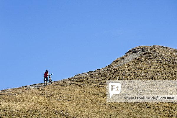 Mountain biker walking bike on uphill in alpine landscape