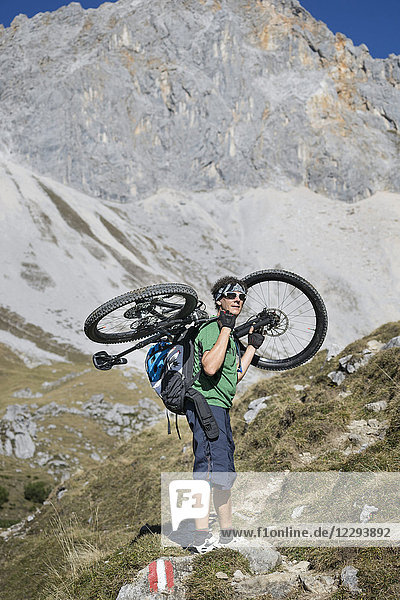 Mountain biker carrying bicycle on his shoulders