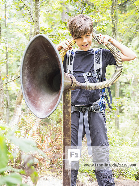 Girl listening to the sounds of the woods with big ear trumpet in black forest  Feldberg  Baden-Württemberg  Germany