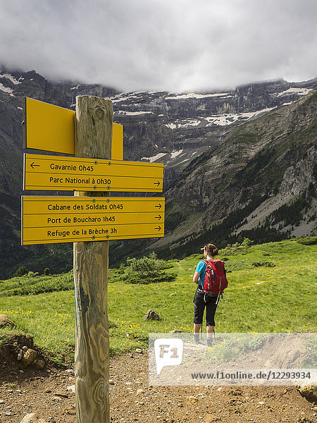 Woman hiking in the High Pyrenees with view over Cirque de Gavarnie  France