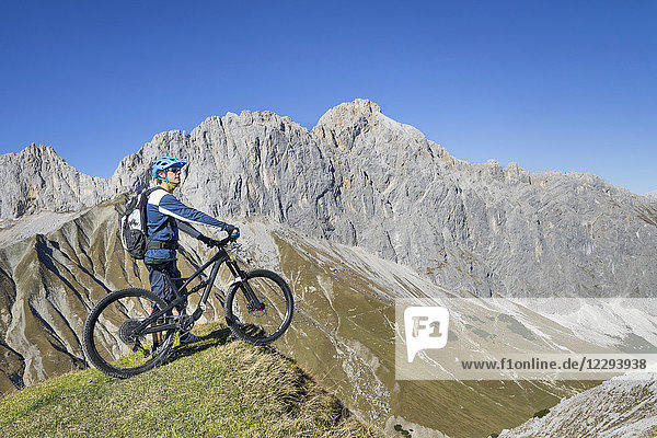 Mountain biker enjoying panoramic view on top of mountain