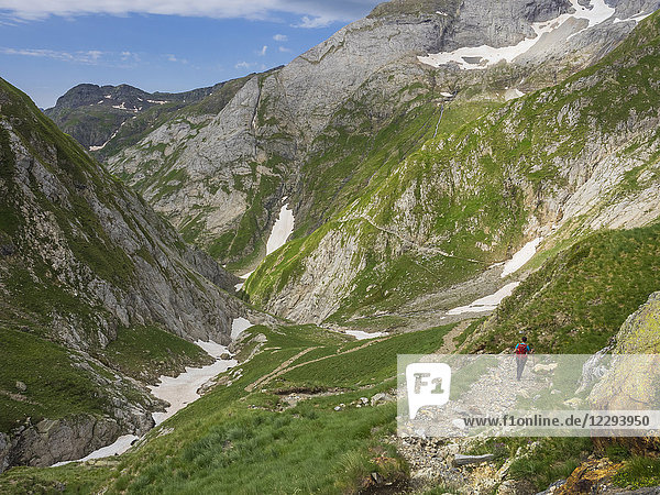 Woman hiking in the High Pyrenees descending from Hourquette d'Ossoue to the valley Barranque d'Ossoue  Gavarnie  France