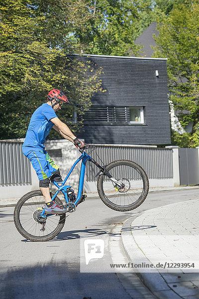 Man doing a wheelie with mountain bike