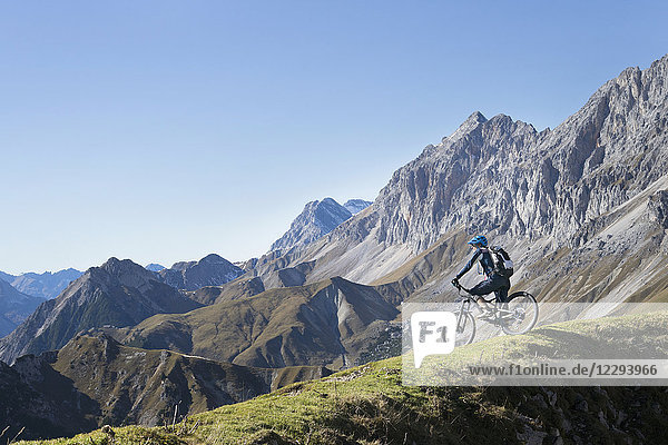 Mountain biker admiring scenic view on top of mountain