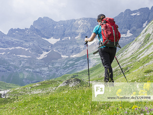Woman hiking in the High Pyrenees enjoying view of cirque d'Estaube,  Gavarnie,  France