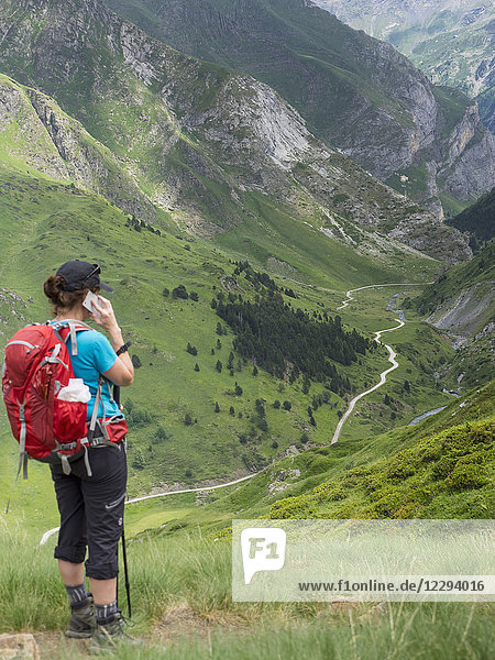 Woman hiker talking on mobile phone in the High Pyrenees  Gavarnie  France