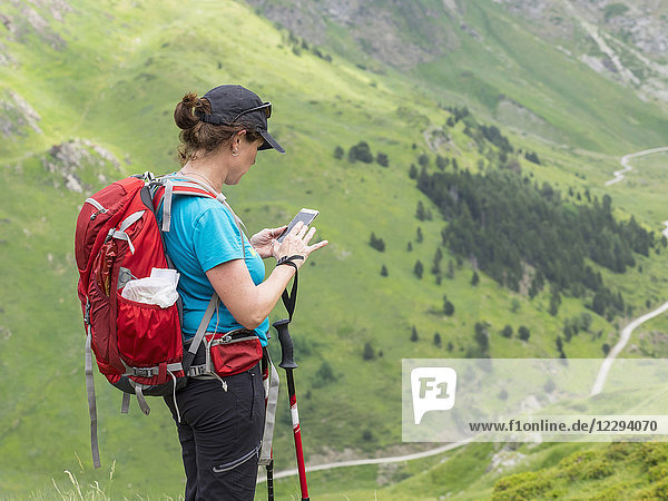 Woman hiker using mobile phone in the High Pyrenees  Gavarnie  France