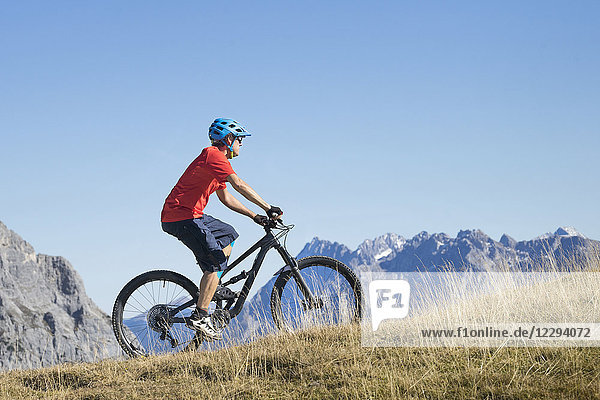 Mountain biker riding on uphill in alpine landscape