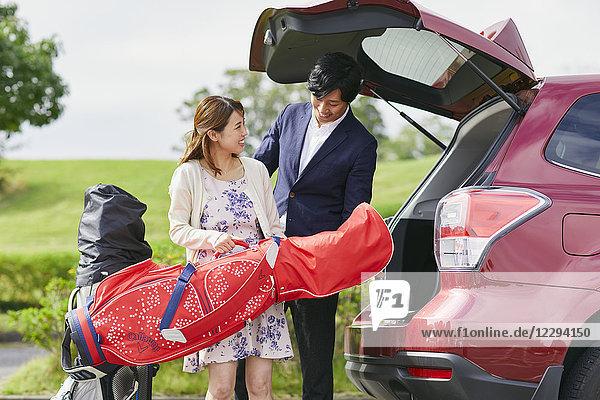 Japanese couple preparing to play golf