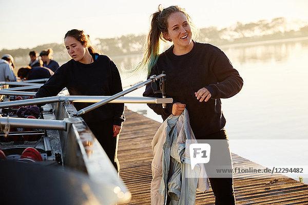 Lächelnde Rudererin bereitet Schädel am sonnigen Seeufer vor