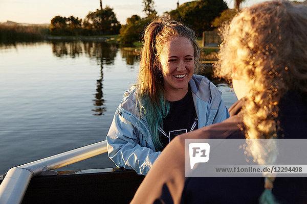 Lächelnde Rudererinnen am sonnigen Seeufer