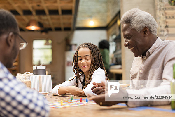 Grandfather and granddaughter playing board game