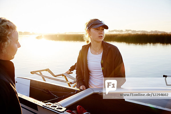 Fokussierte Rudererin beim Heben des Schädels am Sonnenaufgang am Seeufer
