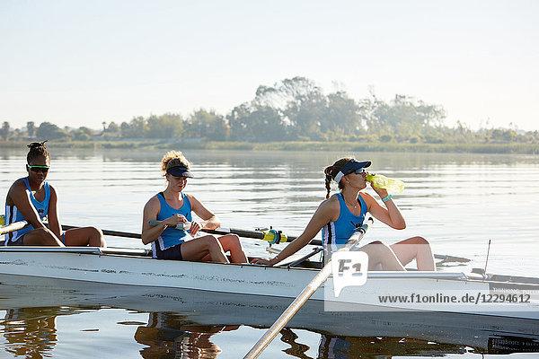 Weibliches Ruderteam ruht  Trinkwasser im Schädel auf dem sonnigen See