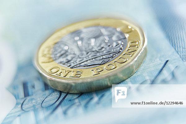 Schließen Sie eine Pfundmünze auf einer Fünf-Pfund-Note.