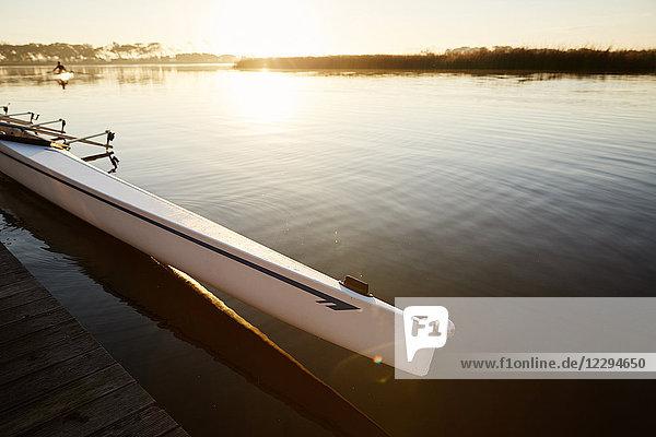 Scull am Dock am ruhigen Sonnenaufgangssee
