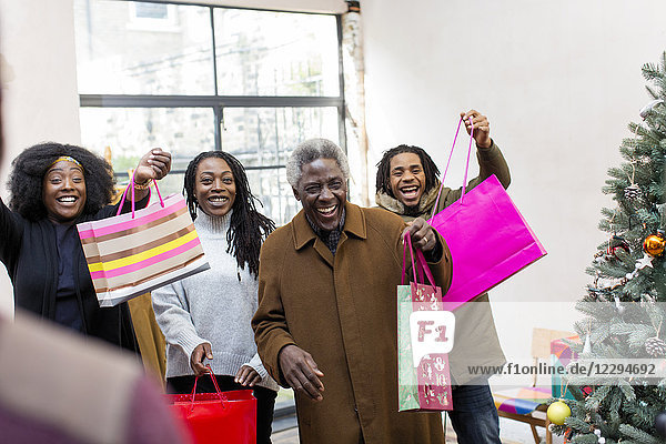 Enthusiastic multi-generation family arriving with Christmas gifts