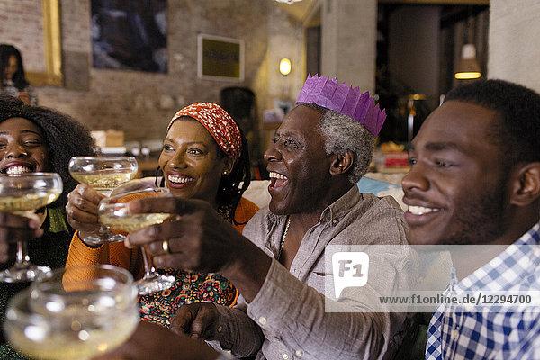 Mehrgenerationen-Familie mit Weihnachtspapierkrone  Toast Champagner
