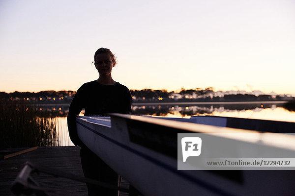 Silhouette des weiblichen Ruderers beim Anheben des Schädels am Sonnenaufgang am Ufer des Sees.