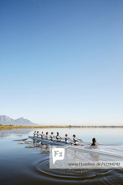 Rudererinnen rudern auf ruhigem See unter blauem Himmel
