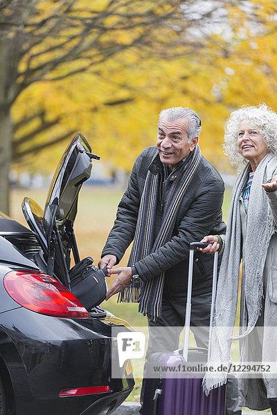 Seniorenpaar  das Gepäck aus dem Kofferraum holt
