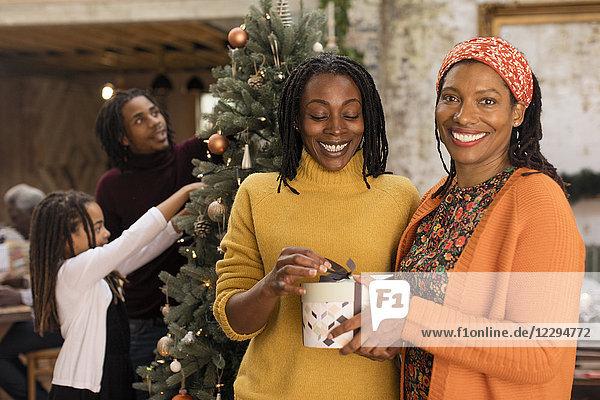Portrait lächelnde Schwestern mit Weihnachtsgeschenk