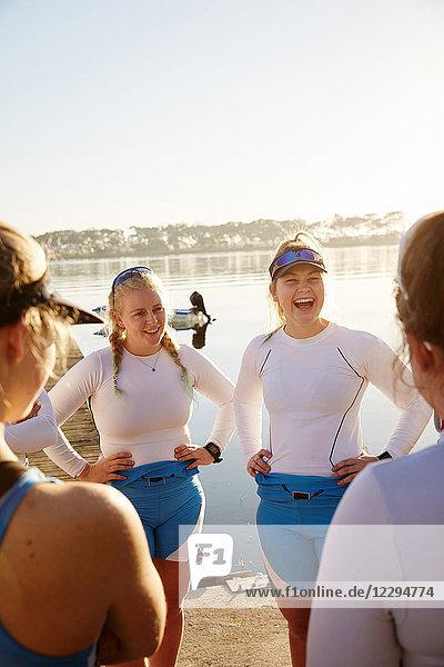 Weibliches Ruderteam lacht und redet am sonnigen Seeufer